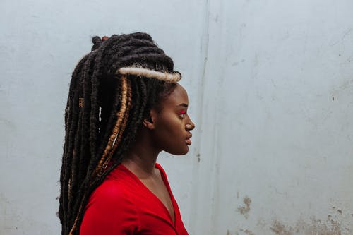 Thoughtful young black woman with dreadlocks looking away against weathered wall