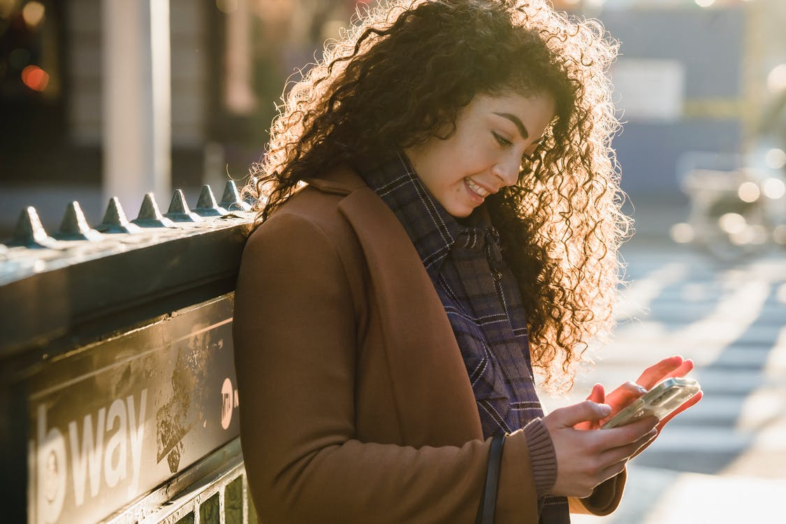 Side view of young female with long curly hair using smartphone intensively on city street on sunny weather