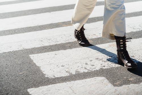 Woman crossing asphalt road on zebra