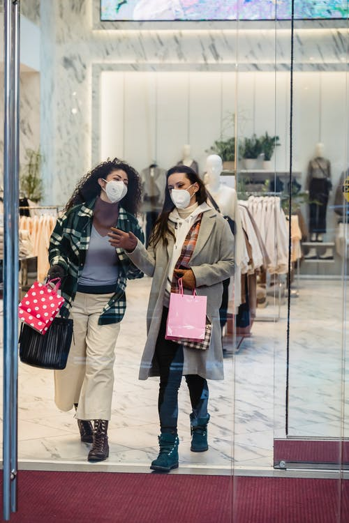 Full body of female friends in protective masks with shopping bags walking through glass doors of clothing store