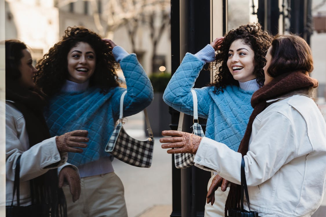 Positive female friends standing together near reflecting wall