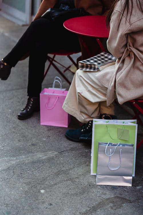 Women sitting at table with various shopping bags