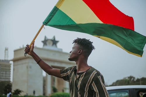 African male with dreadlocks raising flag of Ghana country with colorful stripes while looking away in town
