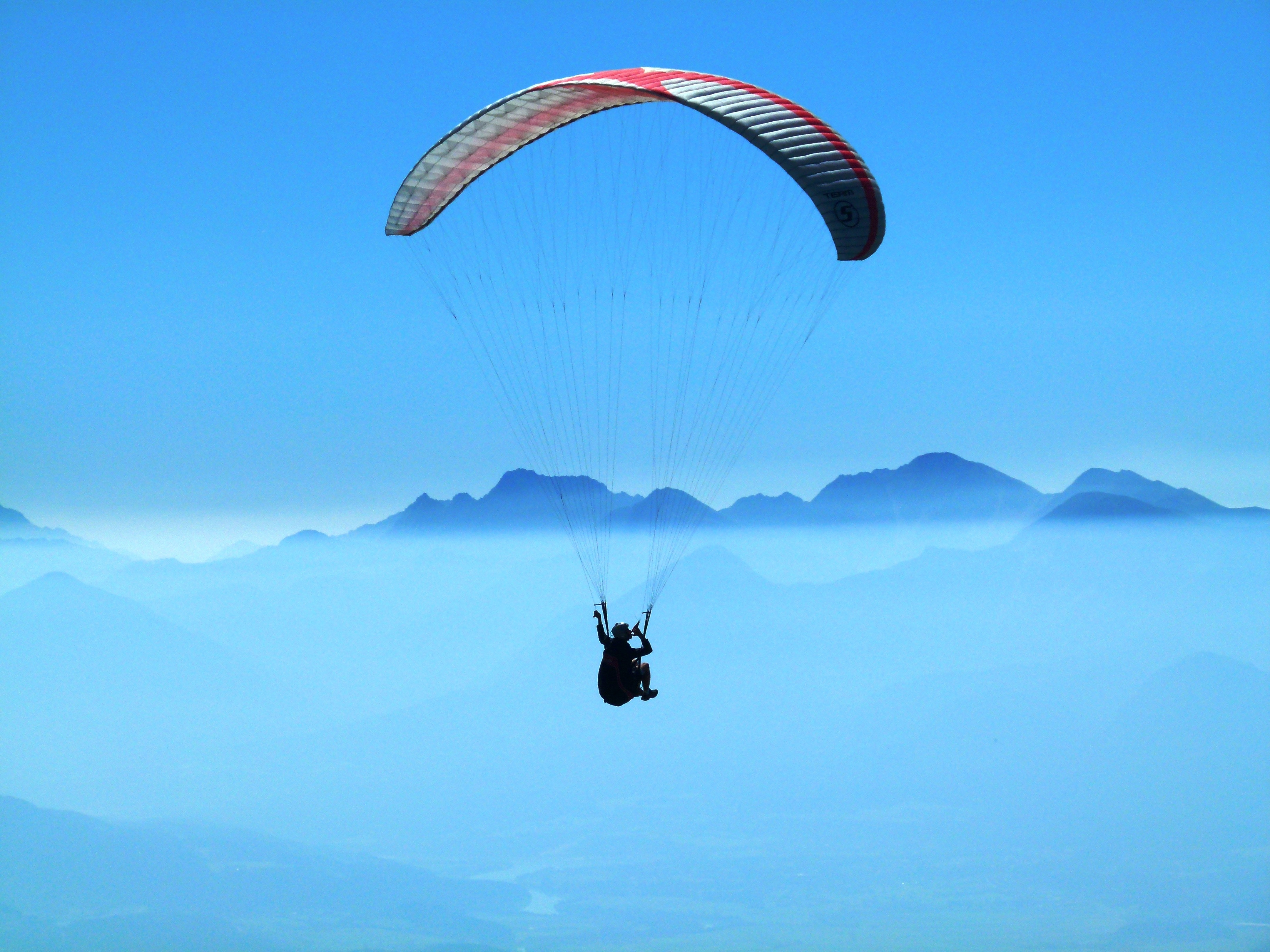 person doing paragliding above clouds during daytime · free stock photo