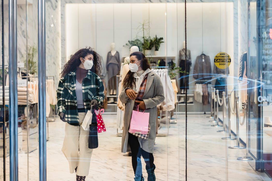 Through glass of female friends in protective masks carrying shopping bags while walking out of clothing store