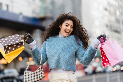 Happy ethnic woman demonstrating shopping bags