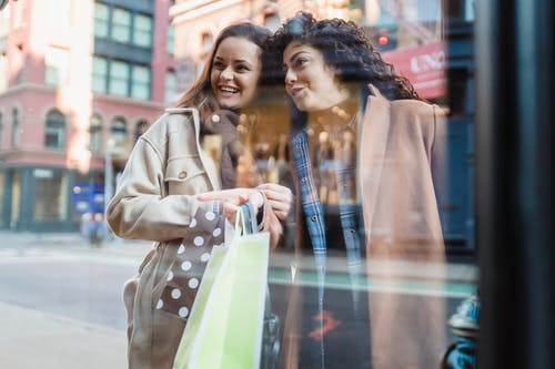 Through glass of cheerful diverse women with shopping bags