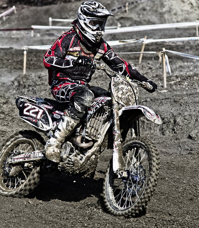 Person Riding on Motorcycle on Motocross Race Track Wearing White and Black Oakley Full Face Helmet during Daytime
