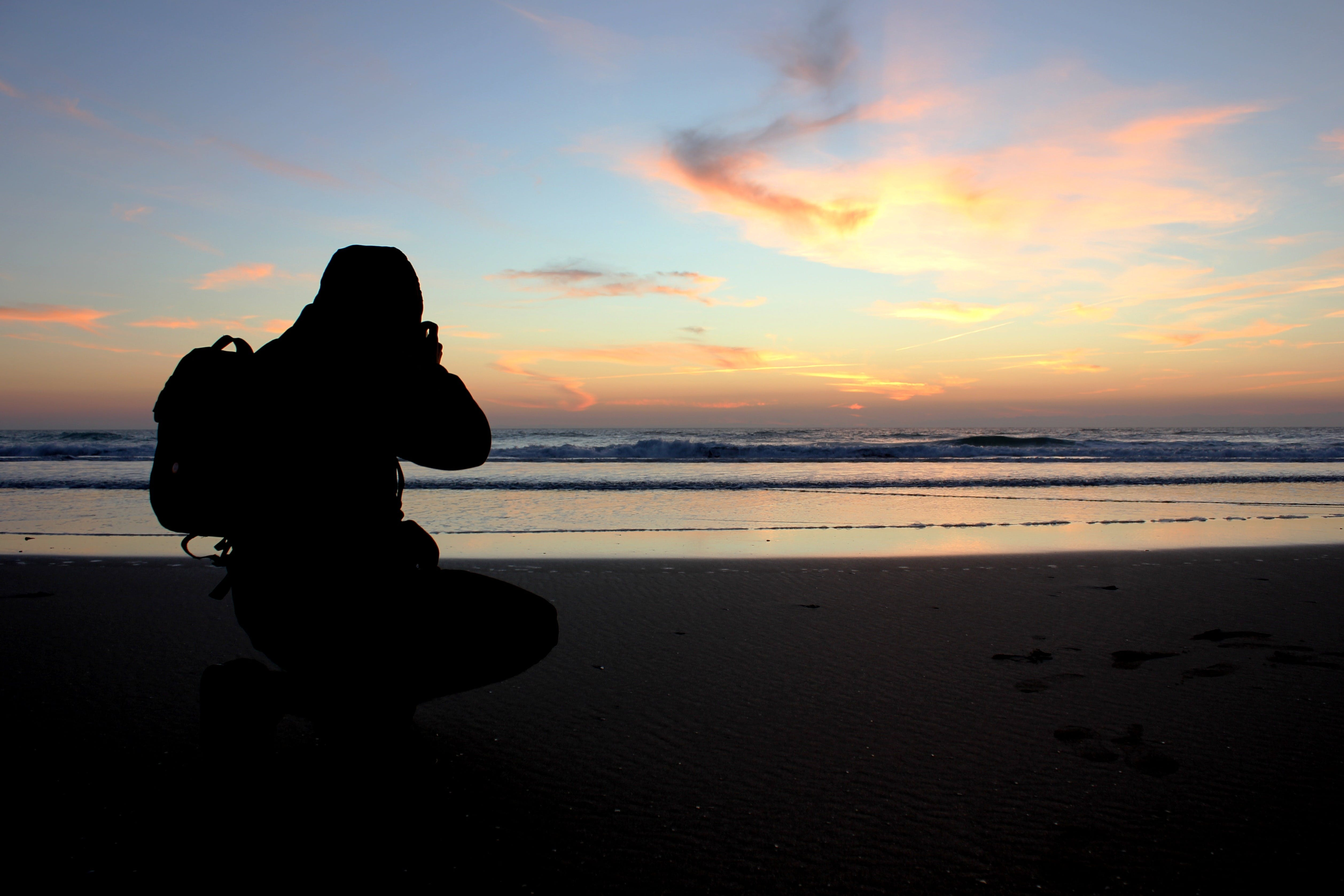 Silhouette of Person Taking Photo Near Ocean