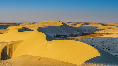 Picturesque landscape of endless desert valley with steep sandy dunes against cloudless sunset sky