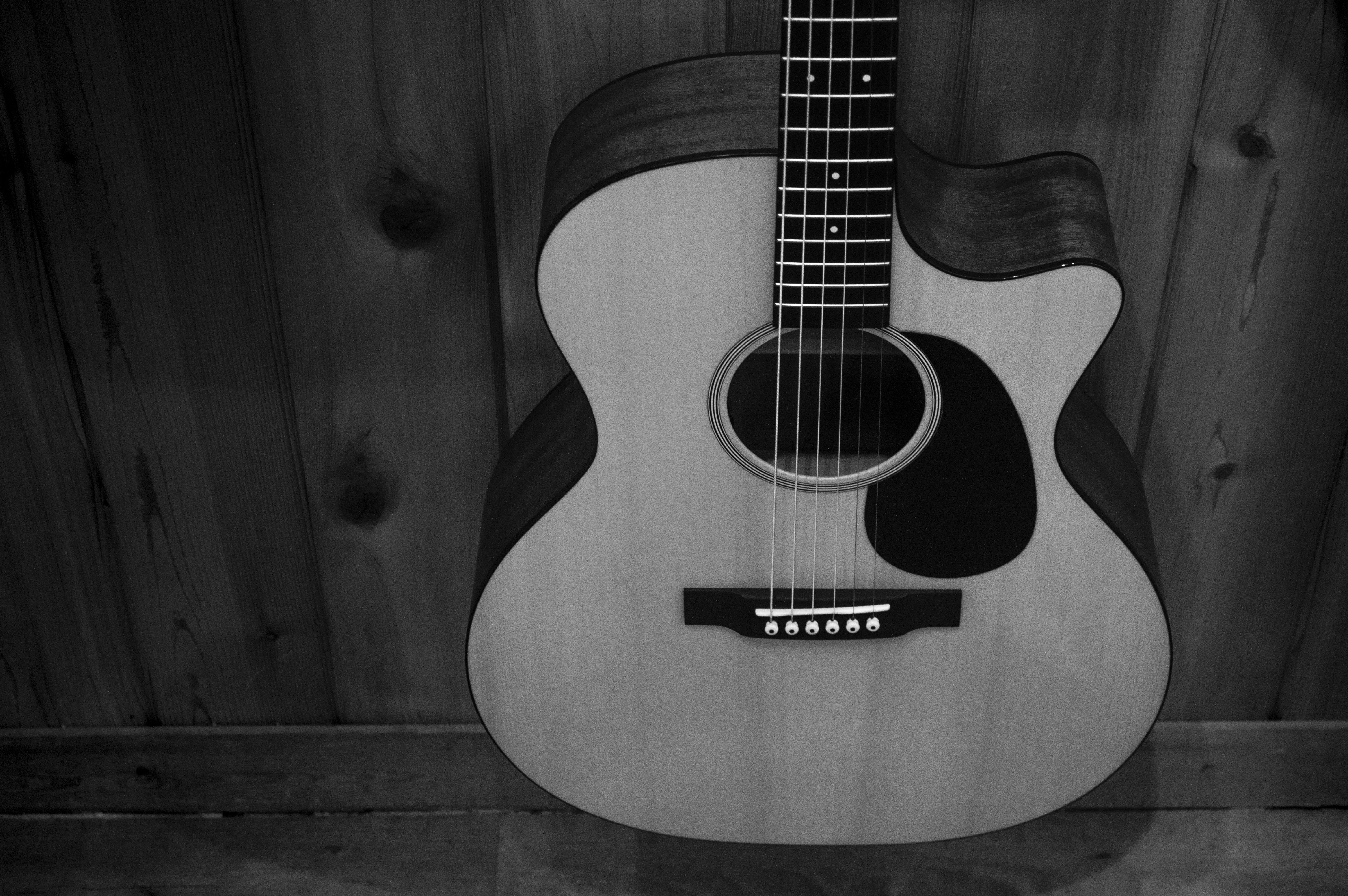 Greyscale Photo of Acoustic Guitar on Wooden Fence