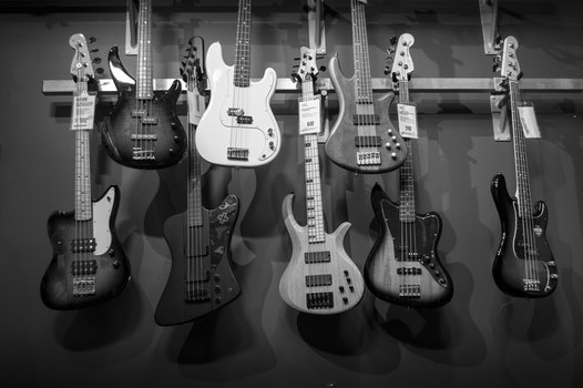 8 Electric Guitars Hanged on Brown Steel Bar