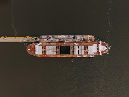 Old metal ship moored near pier
