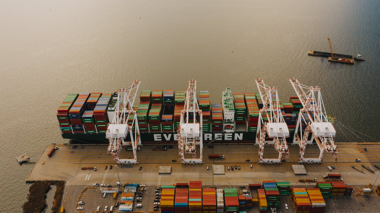 From above of many cargo containers on ship moored on calm water of river in daytime