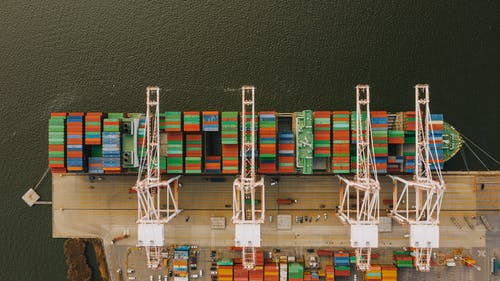 Colorful cargo containers on ship near pier