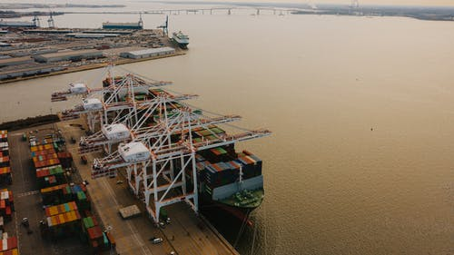 Drone view of cargo containers loaded on long ship on river of pier with lifting cranes