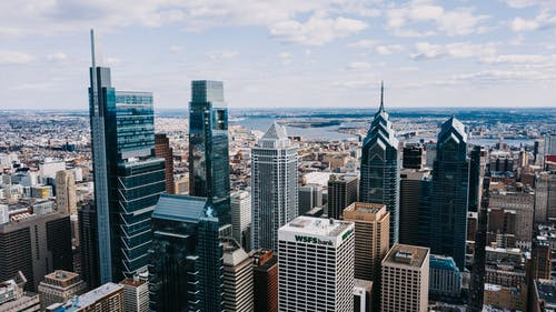 Drone view of modern tall buildings of business centers and offices under tranquil cloudy sky