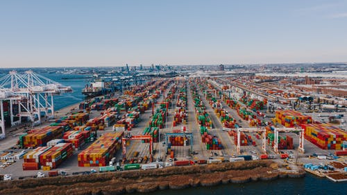 Drone view of river embankment with various bright cargo containers near steel lifting cranes under cloudless sky