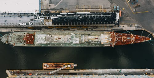 Drone view of long ship moored on water of river near pier in daytime