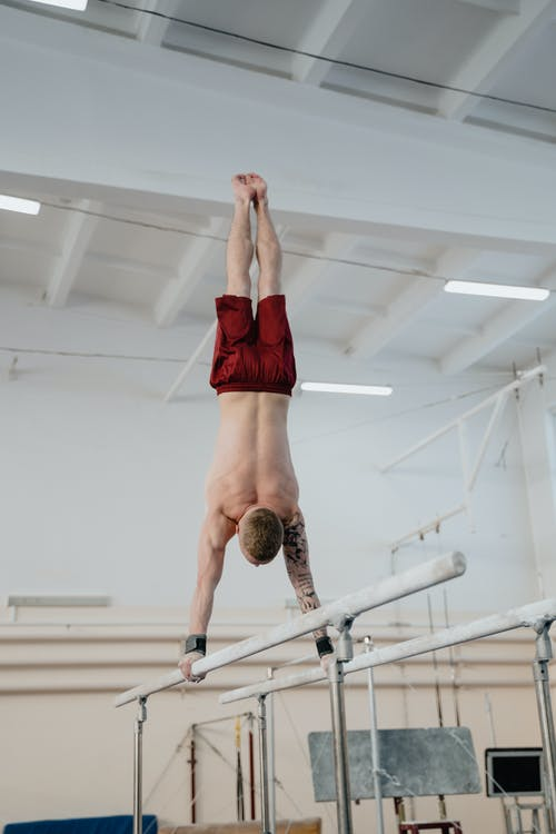 Man Doing Hand Stand on Parallel Bars