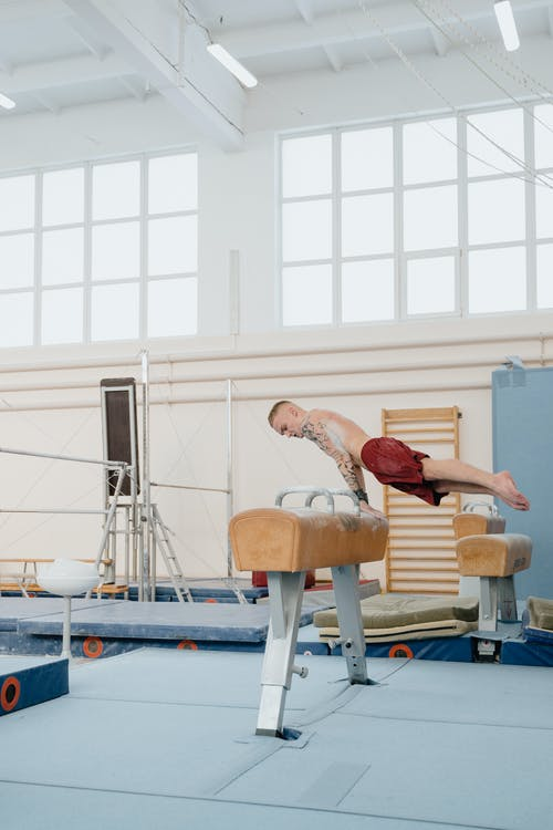 Man Doing Arm Balance on Gymnastics Vault