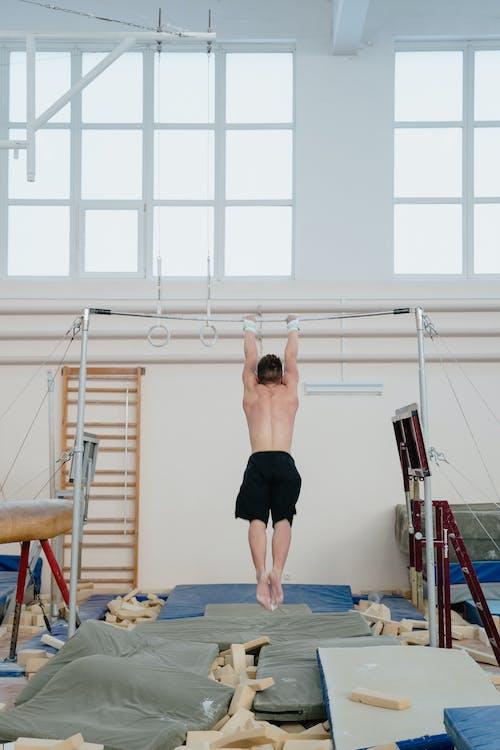Man Hanging on Horizontal Bar