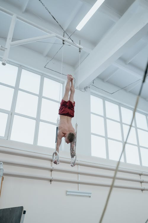 Man Hanging Upside Down on Gymnastics Rings