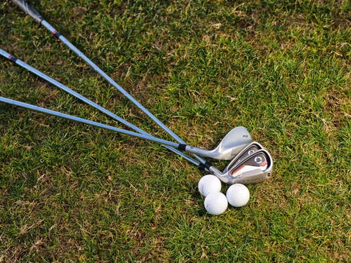 Golf Irons and Balls on Green Grass Field