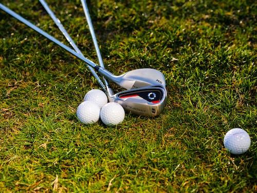 Golf Balls and Golf Clubs on Green Grass