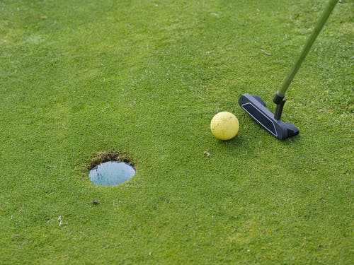 A Golf putter and Ball Near the Green Hole