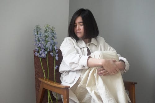 Asian woman in stylish outfit resting in armchair with flowers
