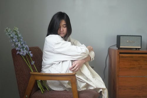 Melancholy Asian female embracing knees while sitting on chair at home