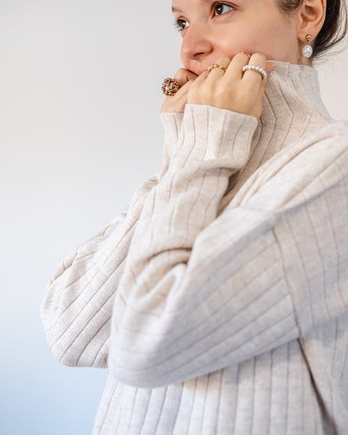 Side view of crop cheerful content female cuddling in collar of soft pullover on white background of studio