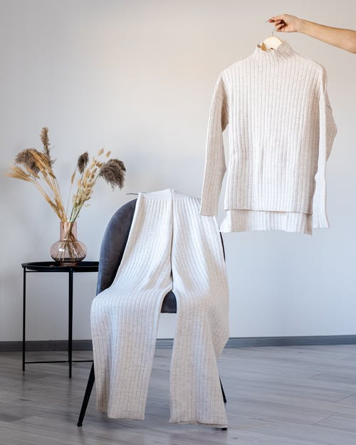 Woman demonstrating woolen pullover on hanger near chair with trousers