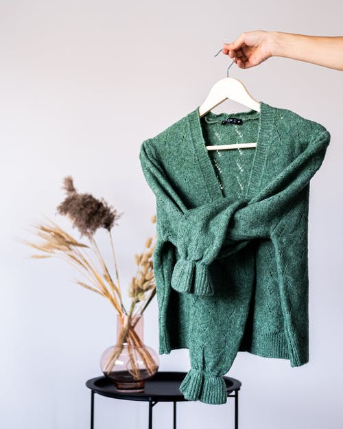 Crop anonymous female demonstrating green woolen pullover on hanger near table with dry plants in glass vase on gray background