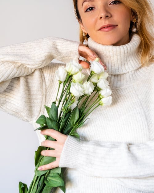 Young happy woman in fashionable sweater with gentle roses