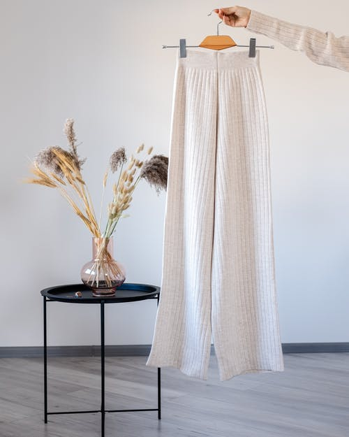 Woman with woolen stylish trousers on hanger