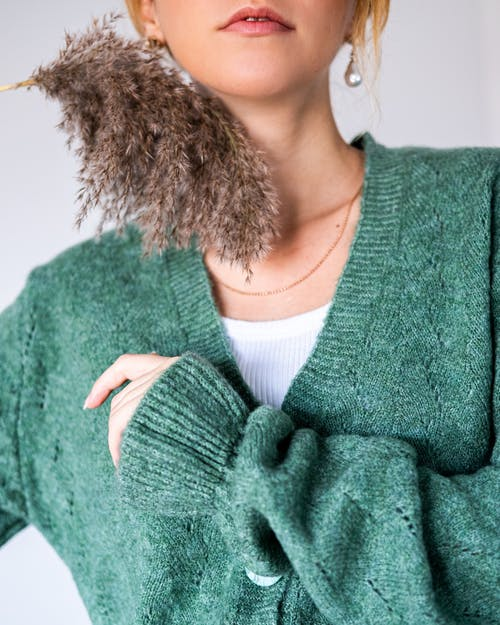 Woman with reed in green woolen cardigan