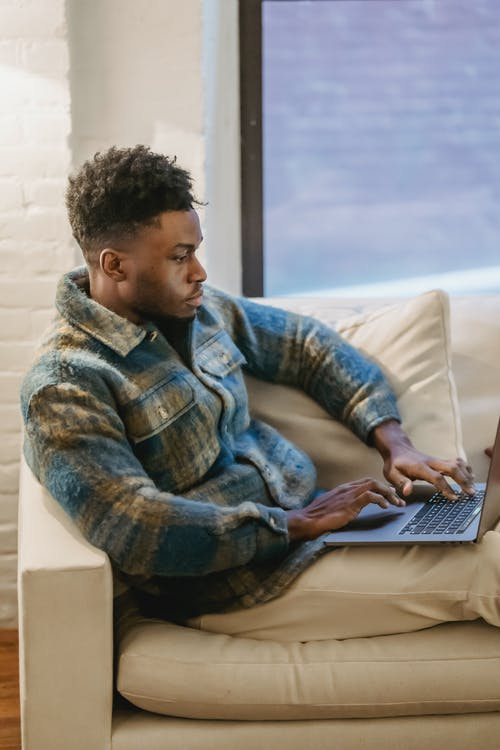 Young focused African American male freelancer in casual clothes sitting on comfortable couch and browsing laptop while working on project remotely in cozy living room