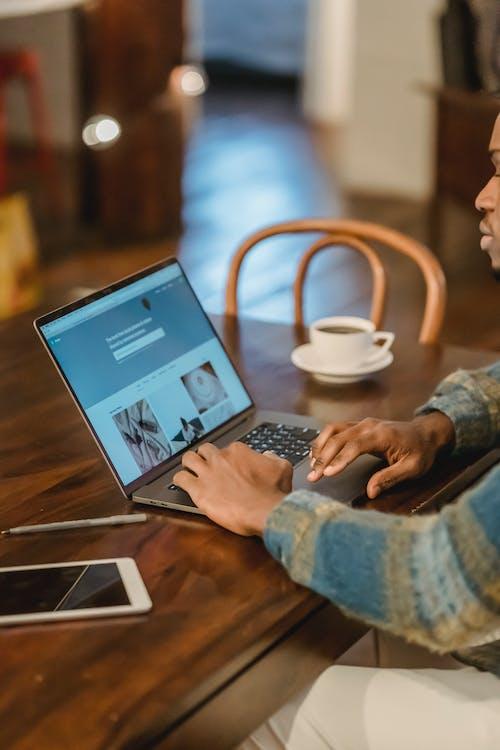 Crop man working on laptop in kitchen