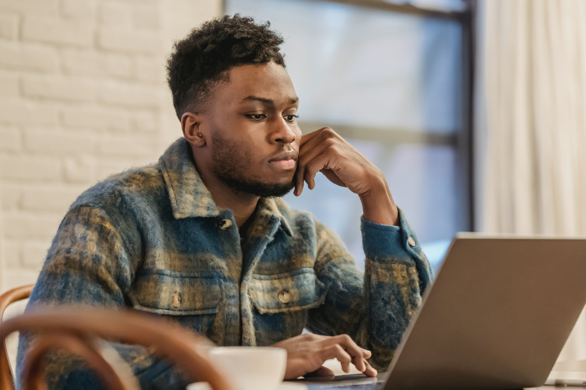 man sitting with his hand on his chin looking at computer