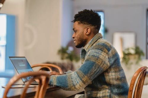 Side view of young bearded black male freelancer with curly hair in casual clothes and sitting at wooden table and browsing netbook while working on project at home