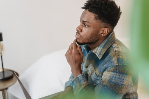 Pensive black man thinking in light room