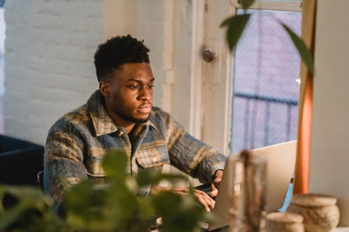 Black bearded man typing on laptop at home