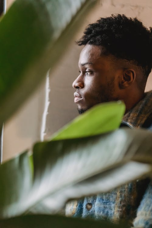 Black man thoughtfully standing before window
