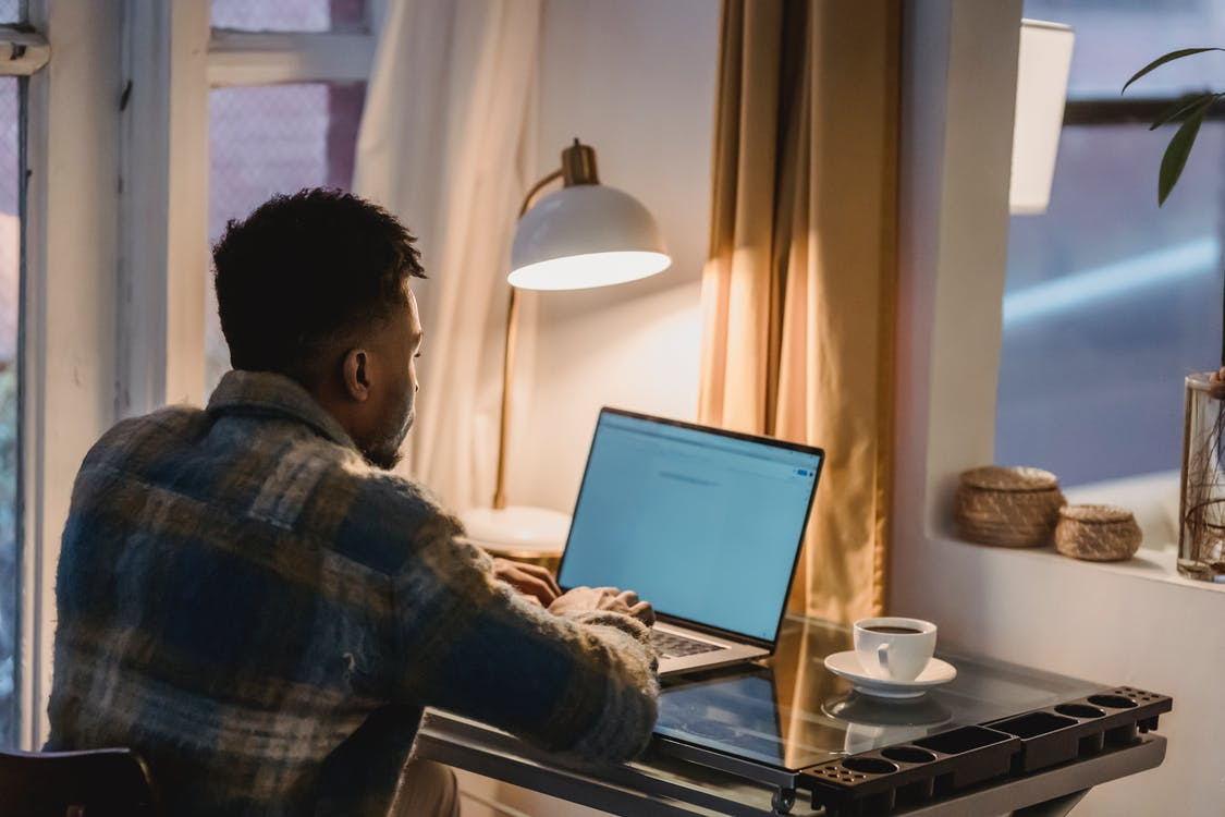 Back view of concentrated African American male typing on keyboard of laptop while sitting at table with cup of coffee and light from lamp
