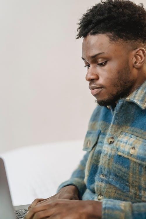 Thoughtful black man typing on keyboard