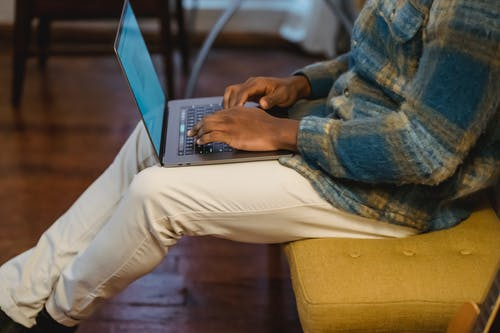 Side view of crop unrecognizable African American male freelancer sitting on yellow banquet and typing on keyboard