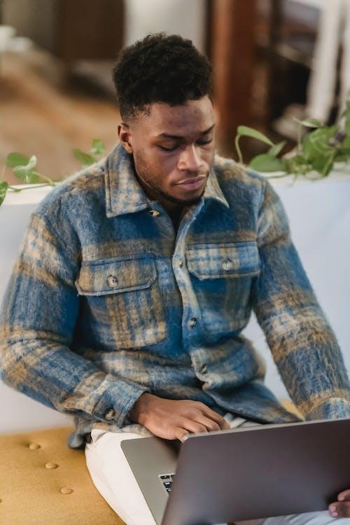 Focused black male freelancer working on laptop