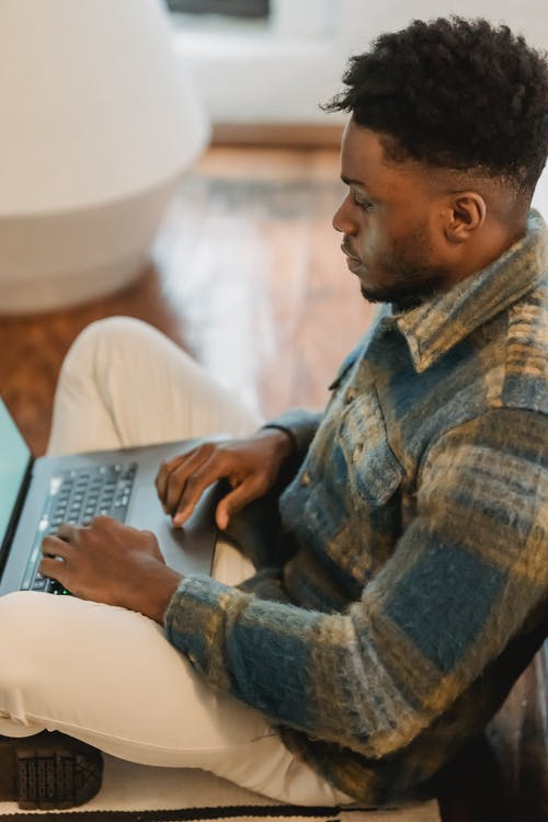 Side view of concentrated African American guy sitting on parquet and browsing laptop while working remotely from home
